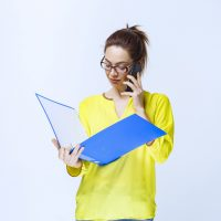 Girl holding a blue folder and positively talking to the phone. High quality photo